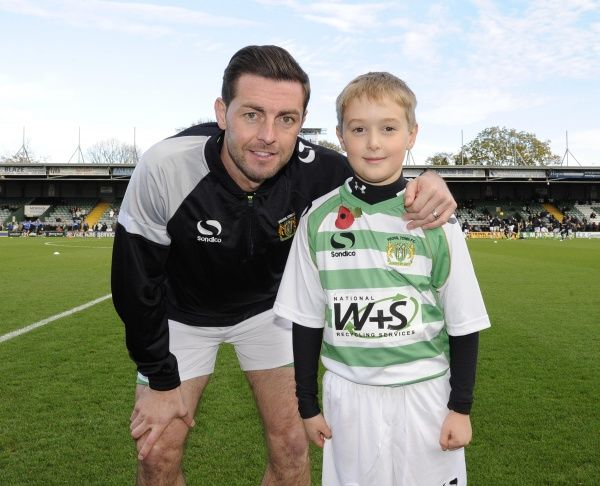Yeovil Town's Jamie McAllister has his photo taken with a young Yeovil Town mascot - Photo mandatory by-line: Dougie Allward/JMP - Tel: Mobile: 10/11/2013 - SPORT - FOOTBALL - Huish Park - Yeovil - Yeovil Town v Wigan Athletic - Sky Bet Championship